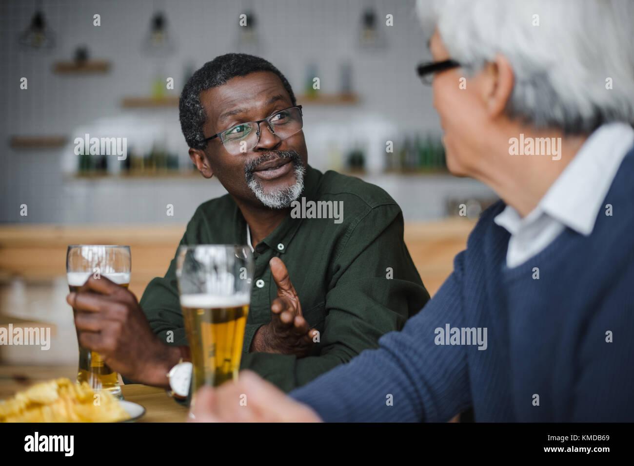 Senior amici di parlare e di bere birra Immagini Stock
