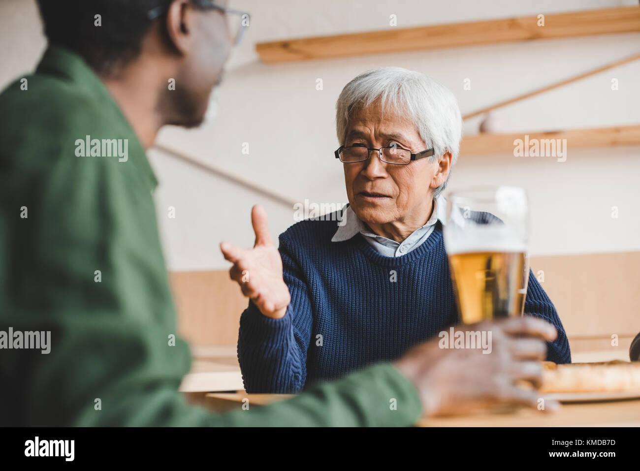 Senior amici avendo discussioni al bar Immagini Stock