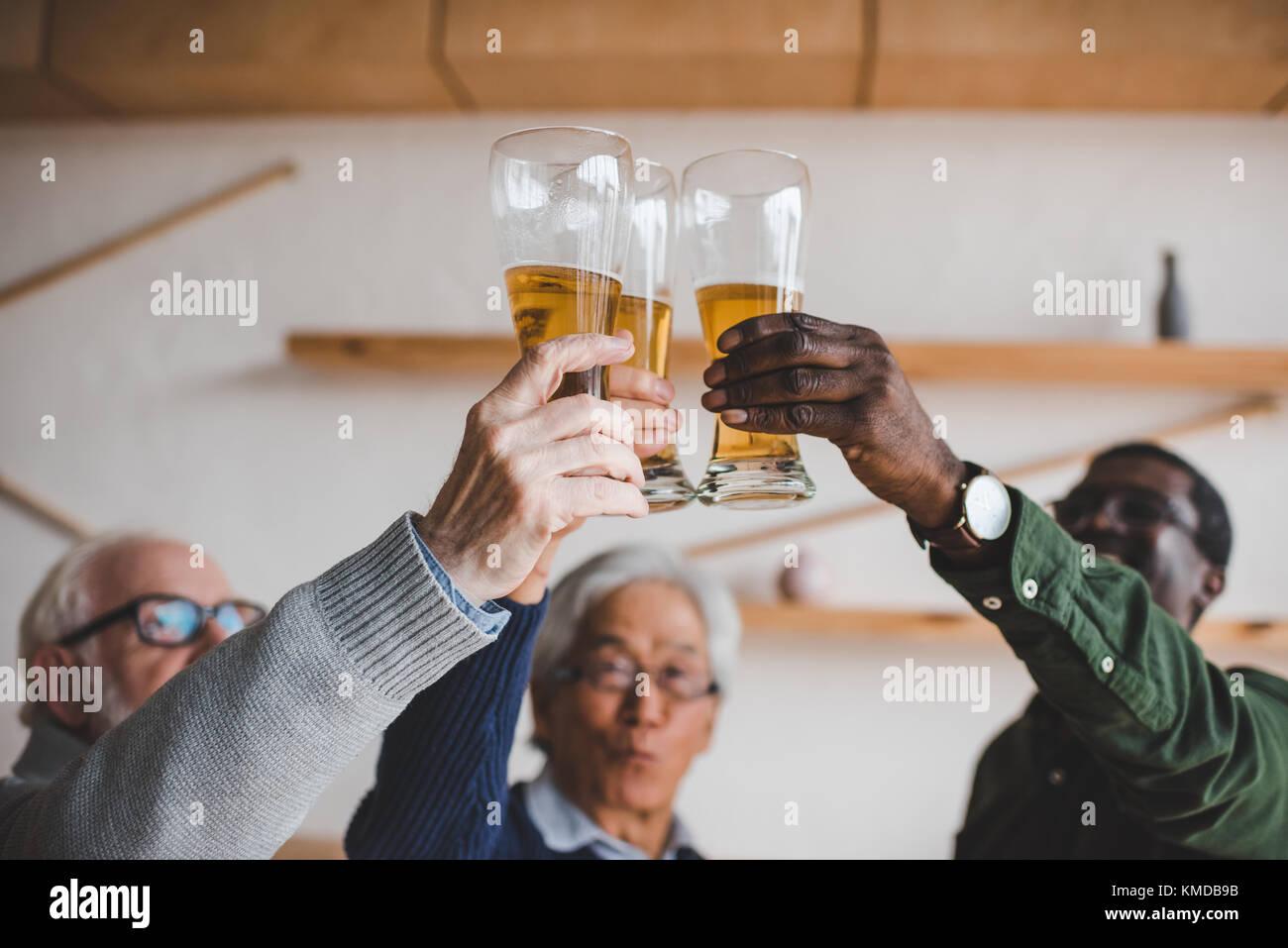 Senior amici tintinnanti bicchieri di birra Immagini Stock