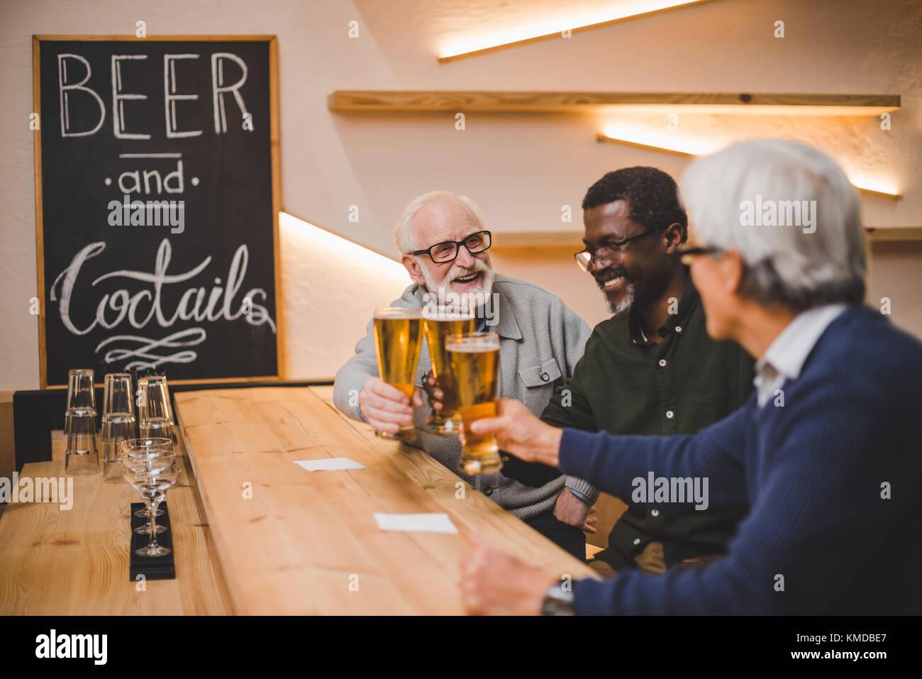Senior gli amici a bere birra insieme Immagini Stock