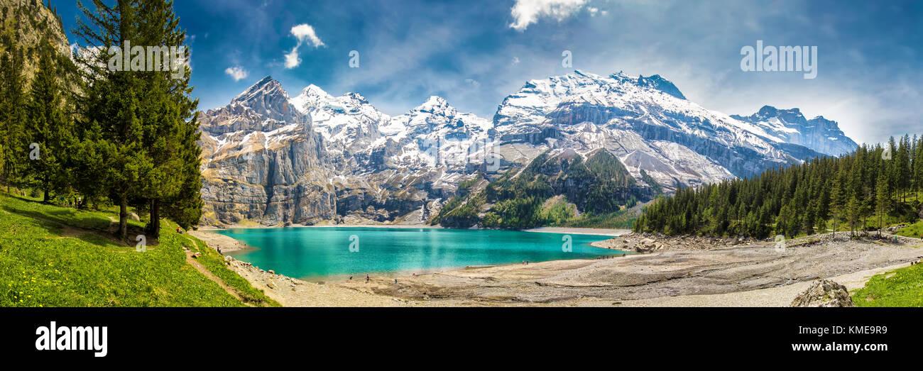 Incredibile tourquise Oeschinnensee con cascate, chalet in legno e Alpi Svizzere, Berner Oberland, Svizzera. Foto Stock