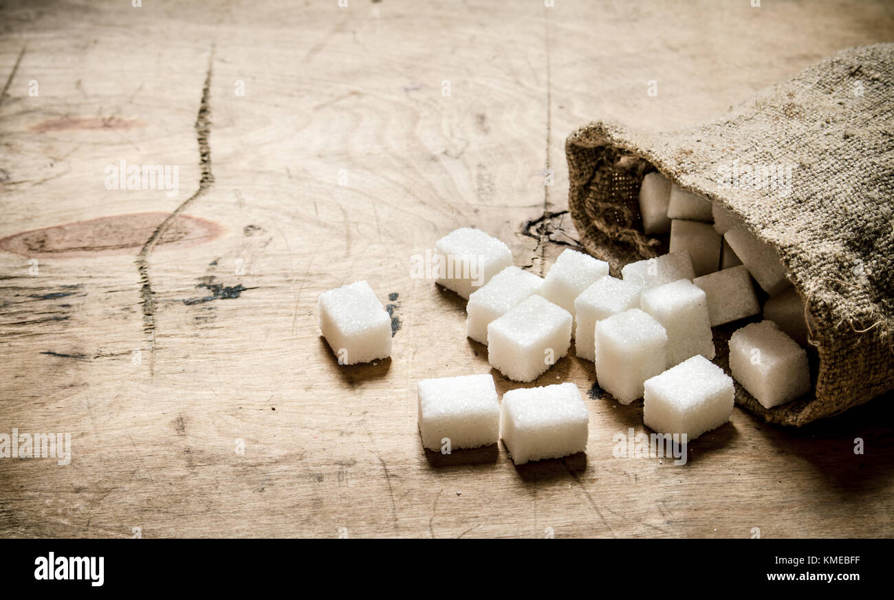 Bianco zucchero raffinato nel sacchetto. Sullo sfondo di legno. Immagini Stock