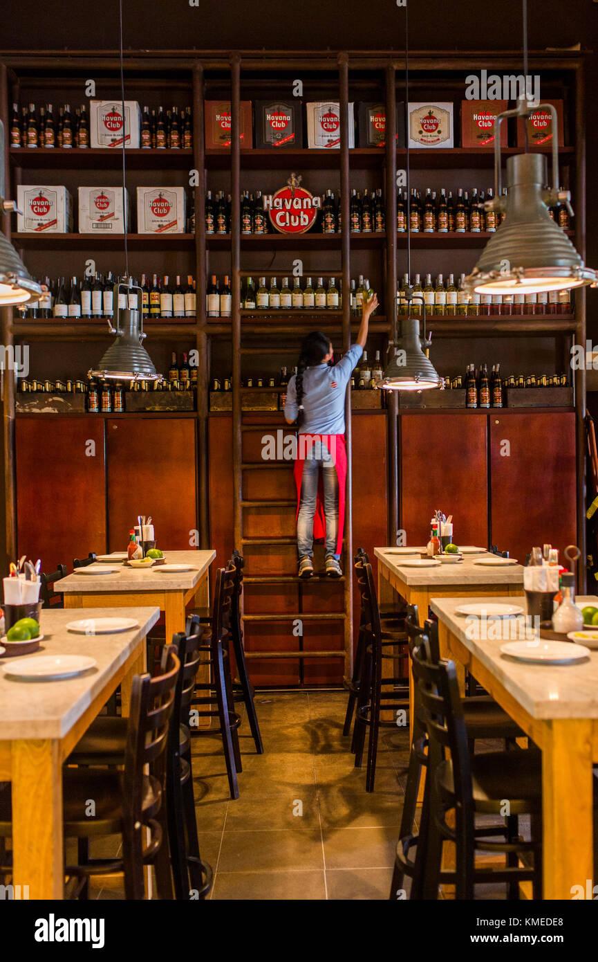 Donna tirando verso il basso la bottiglia di rum a central de cevicheria, ristorante a Bogotà, Colombia Immagini Stock