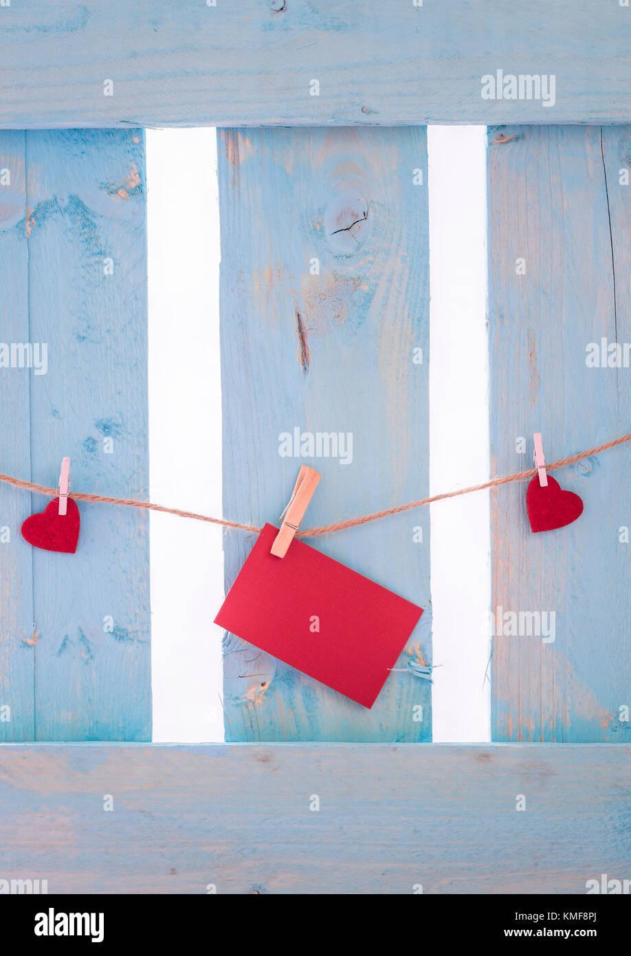 Non scritti carta rossa nota circondato da cuori rossi, legato a una stringa di lino con clip in legno, su un recinto di blu. Foto Stock