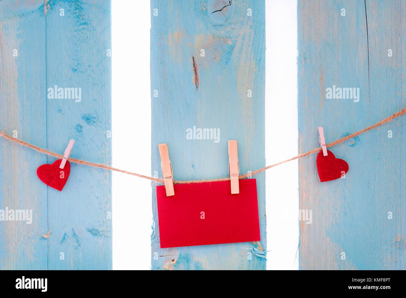 Rosso vuoto scheda messaggio circondato da cuori rossi, legato a una stringa di lino con clip in legno, su un recinto di blu. Foto Stock