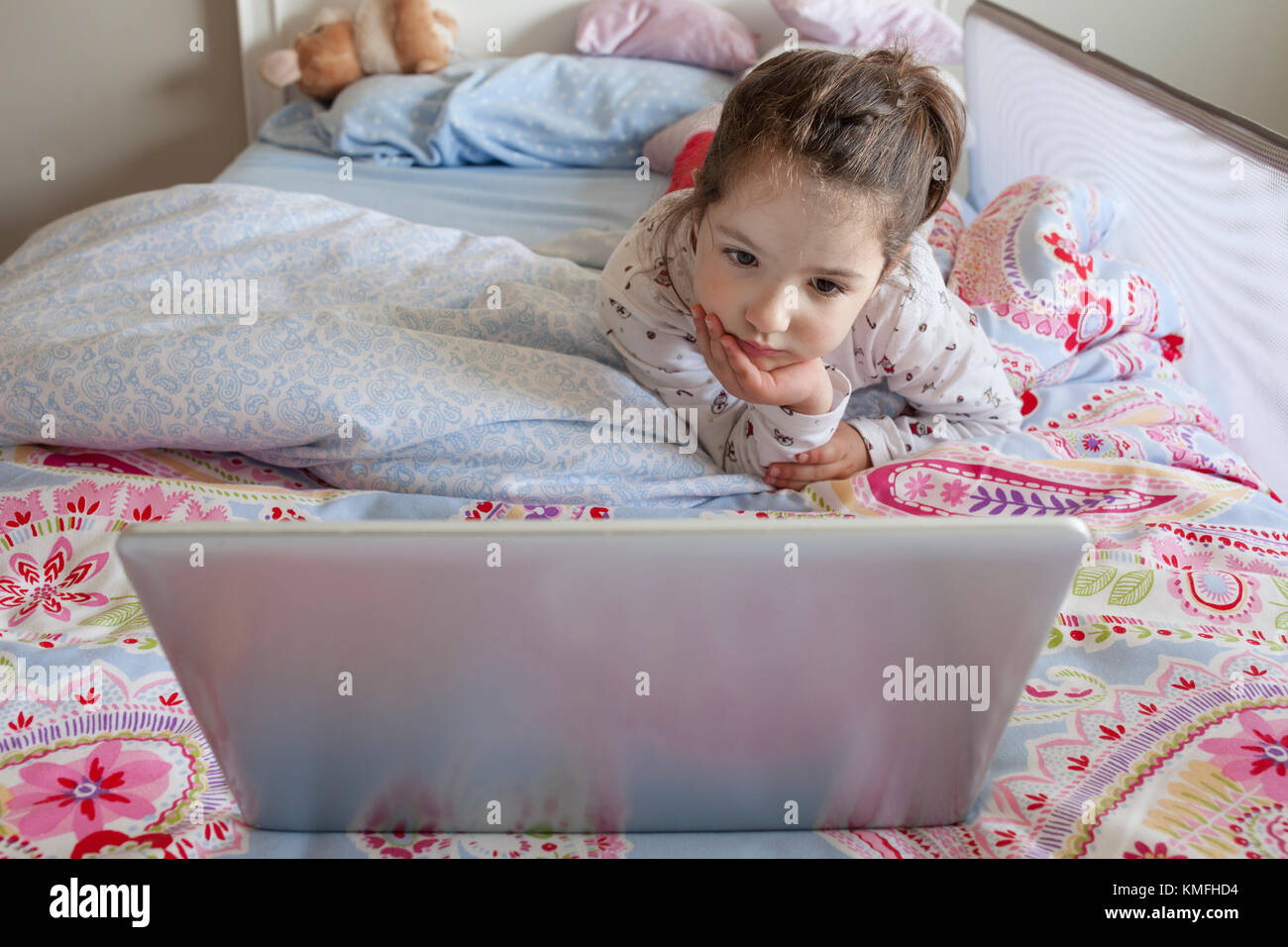 Bambina giacente in letto e giocare con un computer portatile nella sua camera da letto. guarda attento Immagini Stock