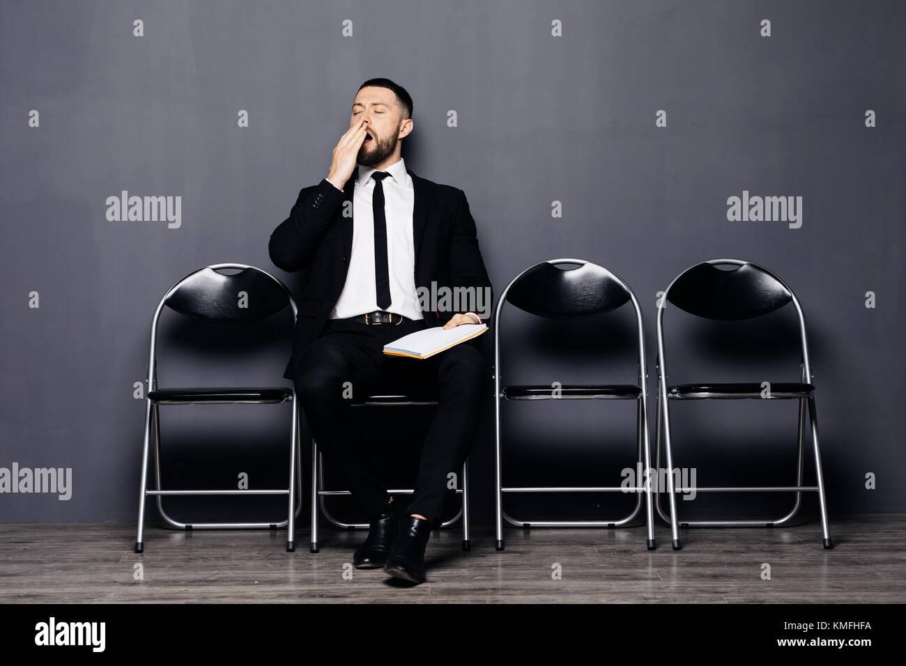 Grave barbuto giovane uomo in bicchieri e abbigliamento formale di imbardata è seduto nella hall sulla sedia Immagini Stock