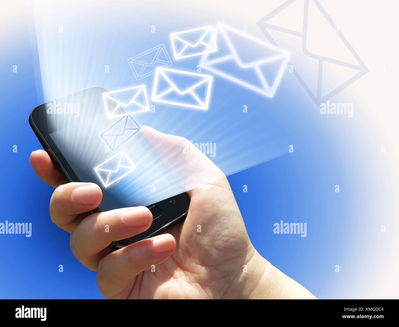 La comunicazione elettronica - invio di messaggi di posta elettronica da un telefono cellulare - mano con lo smartphone Immagini Stock