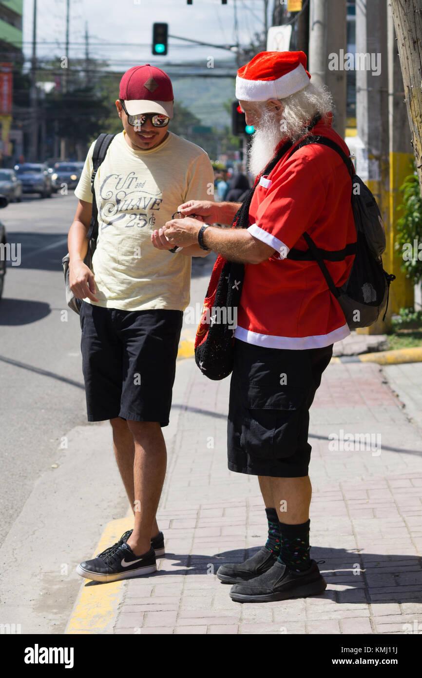 Cittadino usa ray shackelford dresssed in santa outfit,dando dei piccoli doni per i passanti a Cebu City, Filippine Immagini Stock