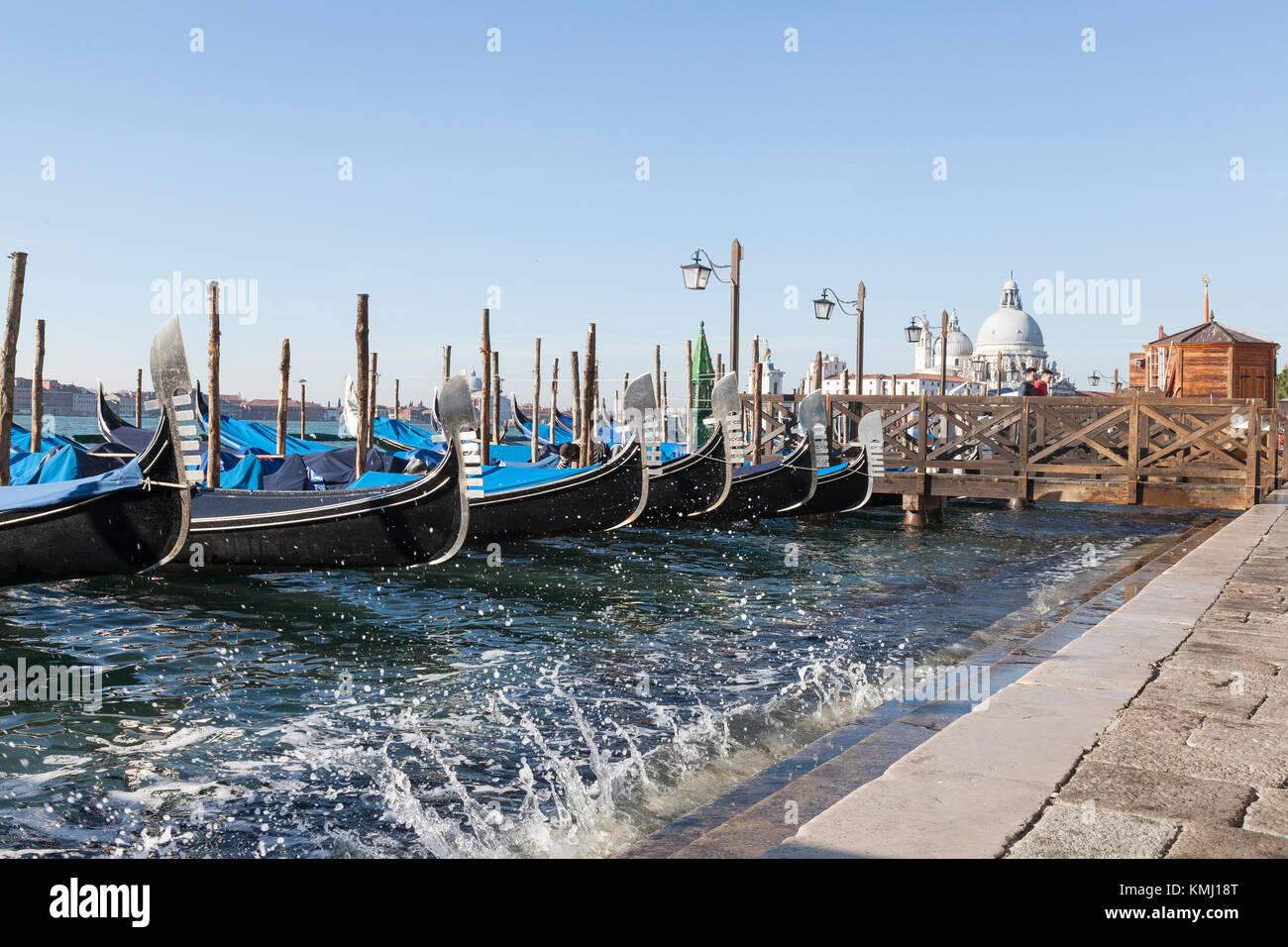 Gondole a San Marco in sella ad alto contenuto di acqua su un Acqua alta marea con spruzzi e una vista di Baslica di Santa Maria della Salaute, Venezia, Italia Foto Stock
