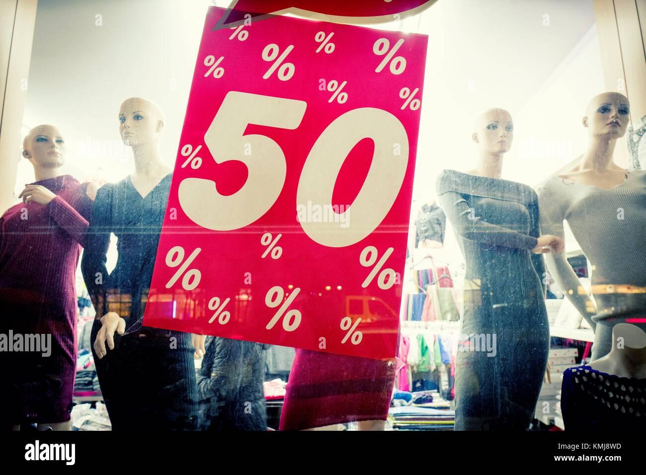 Il Primer plano de onu escaparate de una tienda de moda con maniquís femeninos y onu cartello grande de 50. Immagini Stock