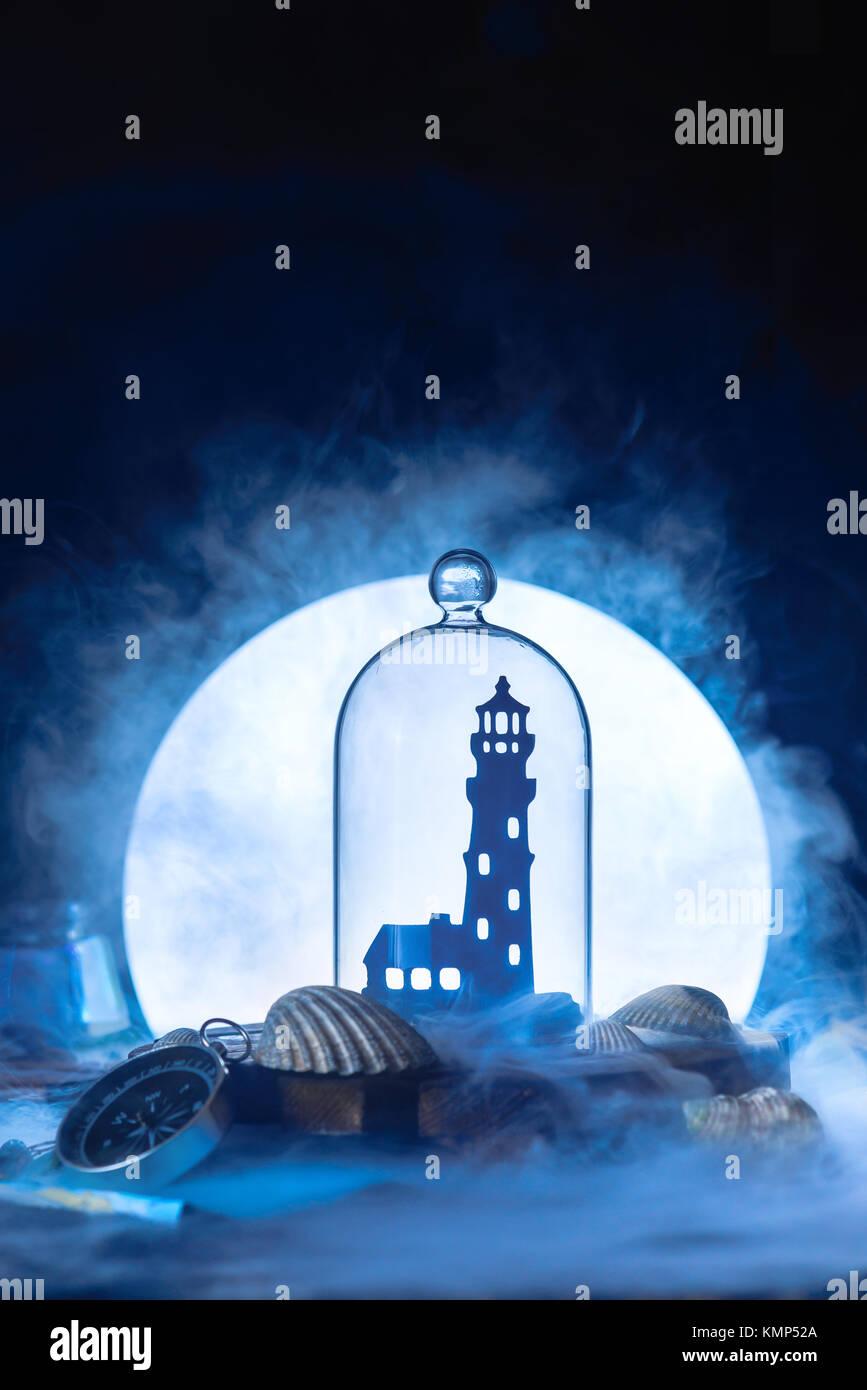 Mare ancora in vita con faro silhouette in luna piena. Notte scena oceano con fumo su acqua e copia dello spazio. Immagini Stock