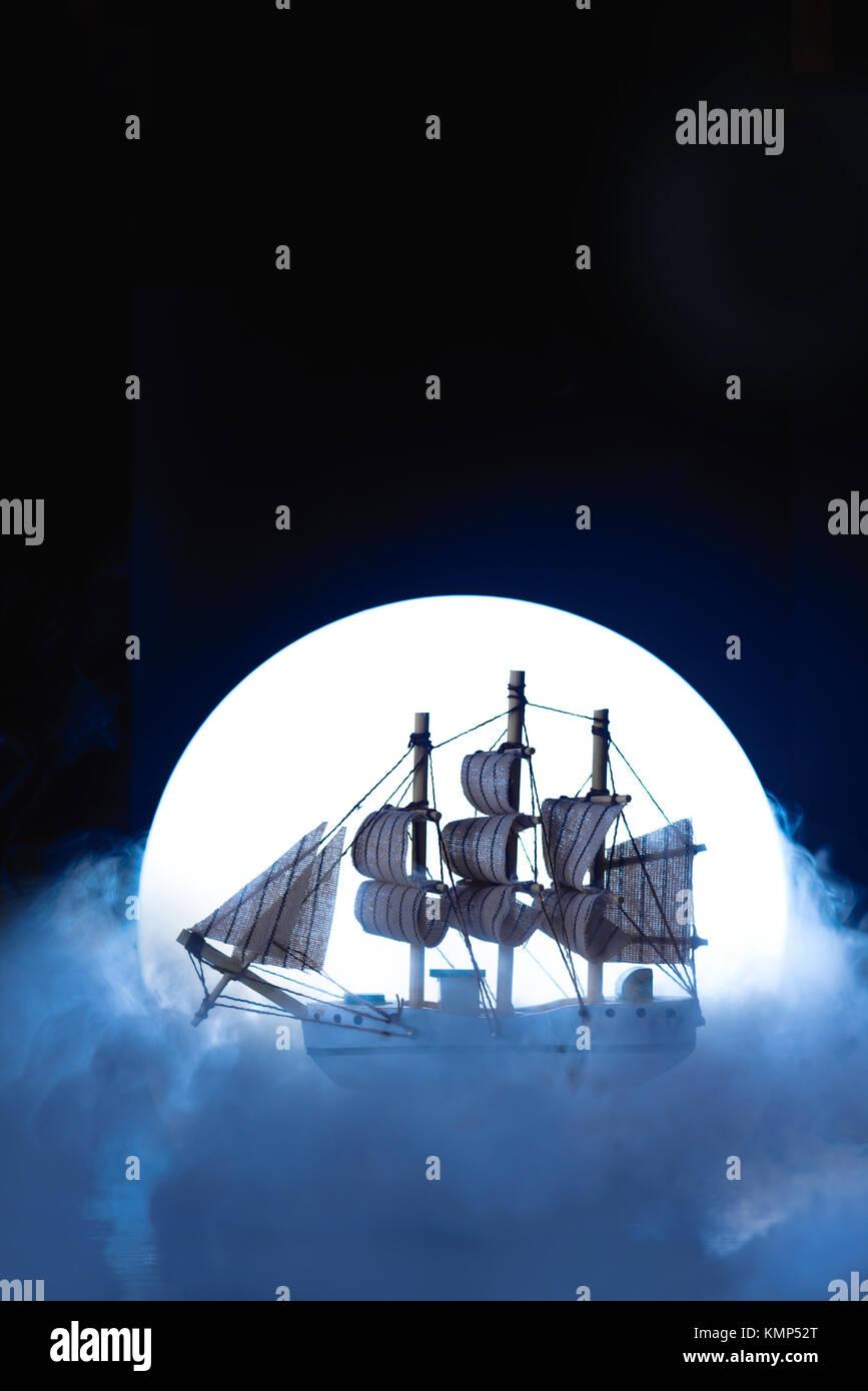 Nave a vela nella luce della luna piena. Modello in legno su sfondo scuro. Marine concettuale ancora in vita. Immagini Stock