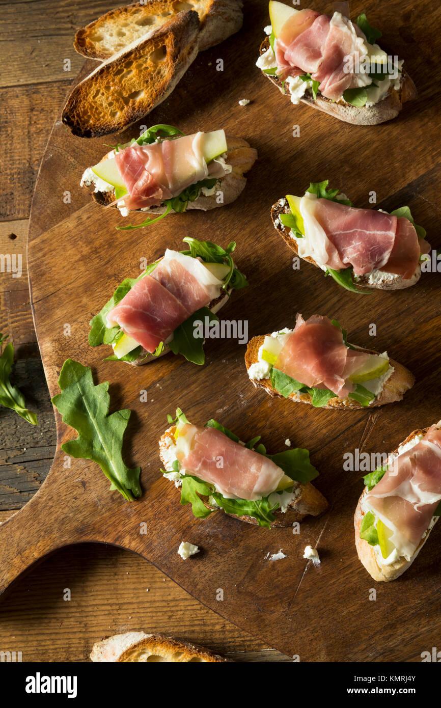 Il prosciutto casalingo Pera Crostini di formaggio con rucola Immagini Stock