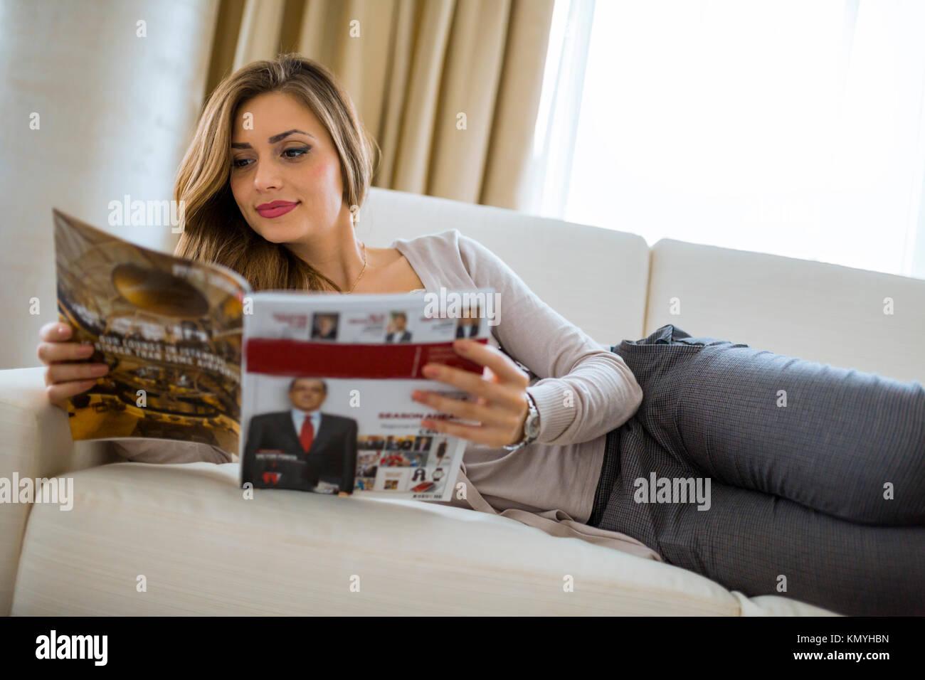 Bella donna su un divano, la lettura di una carta di soggiorno Foto ...