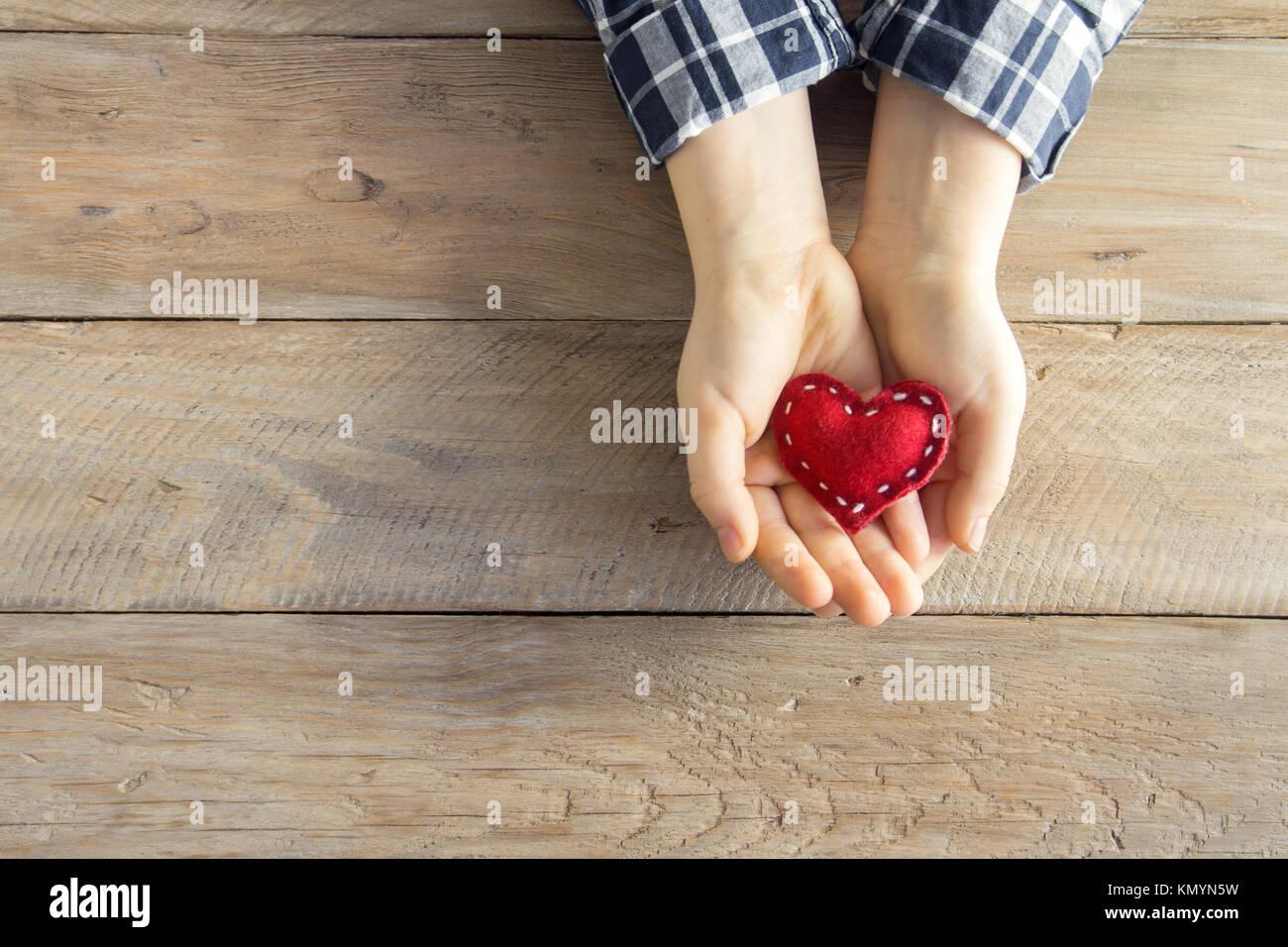 Cuore rosso nel bambino con le mani su sfondo di legno, copia dello spazio. Gentilezza, di amore e di carità Immagini Stock