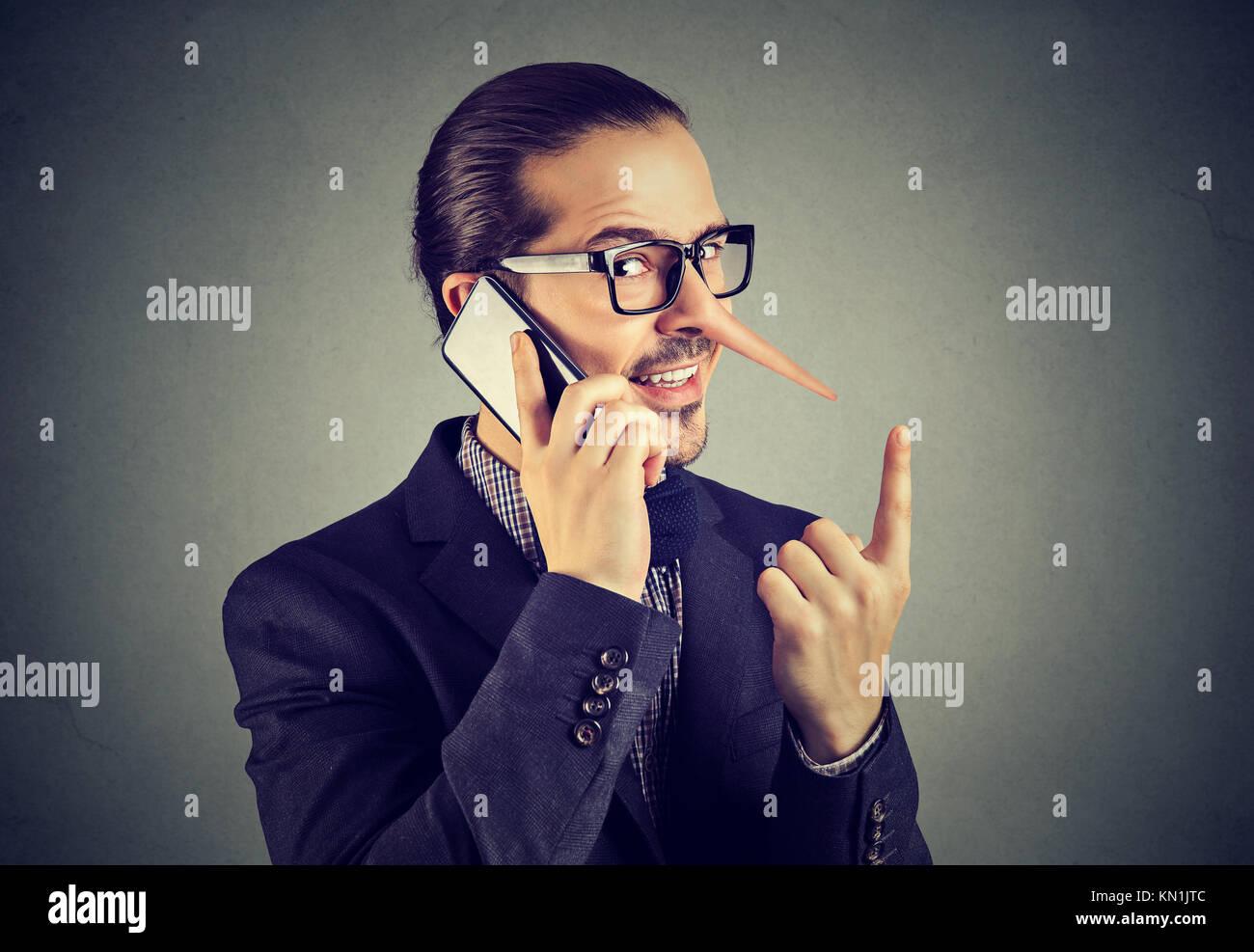 Sly bugiardo business man con il naso lungo parlando al telefono cellulare isolata sul muro grigio Sfondo. Immagini Stock