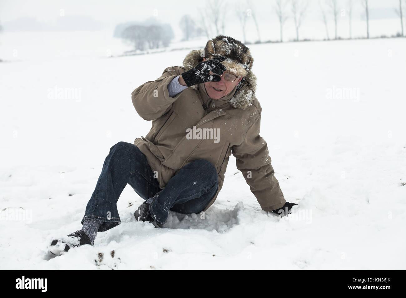 Senior uomo incidente cadendo sulla neve in inverno. Foto Stock