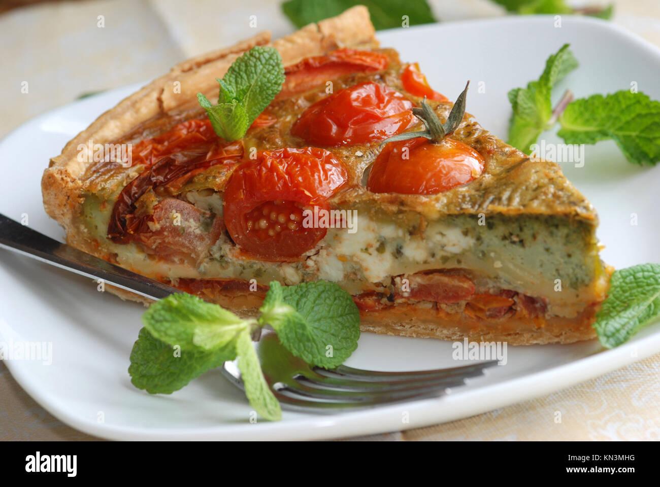Preparata di fresco di pomodoro, basilico e pesto quiche. Immagini Stock
