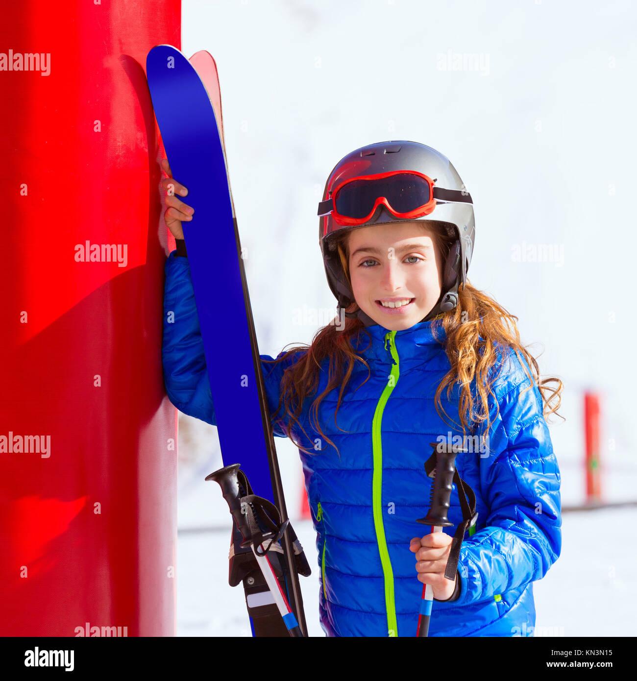 Kid girl neve invernale con attrezzature da sci casco occhiali poli. Immagini Stock