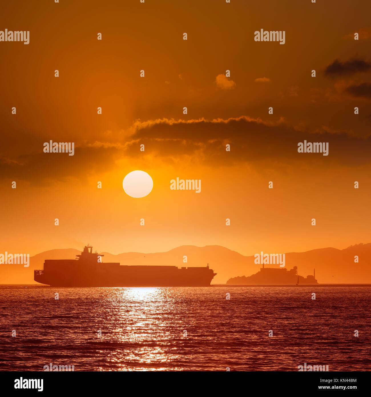 Isola di Alcatraz penitenzieria al tramonto e la nave mercantile in San Francisco California USA. Immagini Stock