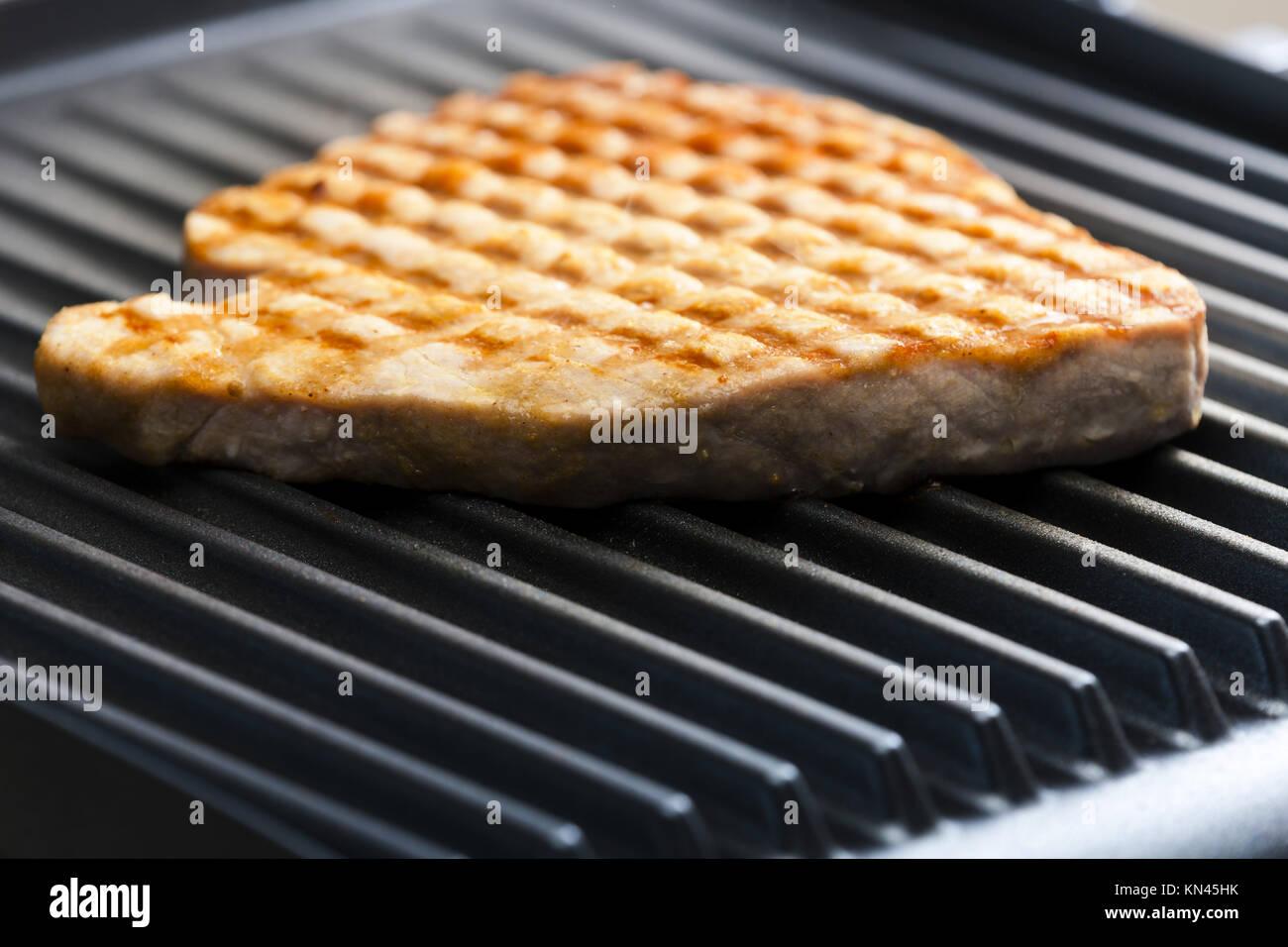 Bistecca di tonno sulla griglia elettrica. Immagini Stock