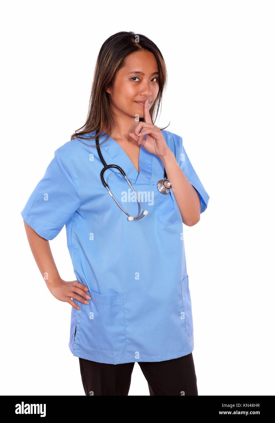 Ritratto di un affascinante infermiera asiatica donna con uno stetoscopio richiesta di silenzio sul blu uniforme Immagini Stock