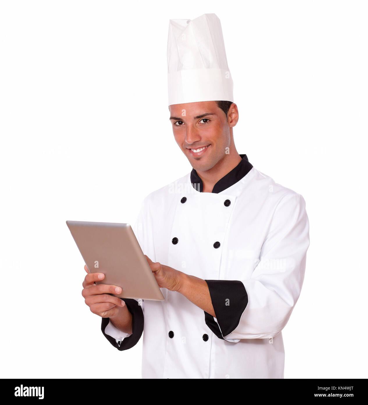 Ritratto di professional 20s chef uomo su bianco uniforme utilizzando il suo tablet pc mentre sorridente a voi su Immagini Stock