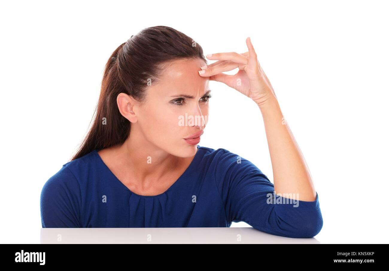 Gentile ragazza in maglietta blu guardando imbarazzato in sfondo bianco - copyspace. Immagini Stock