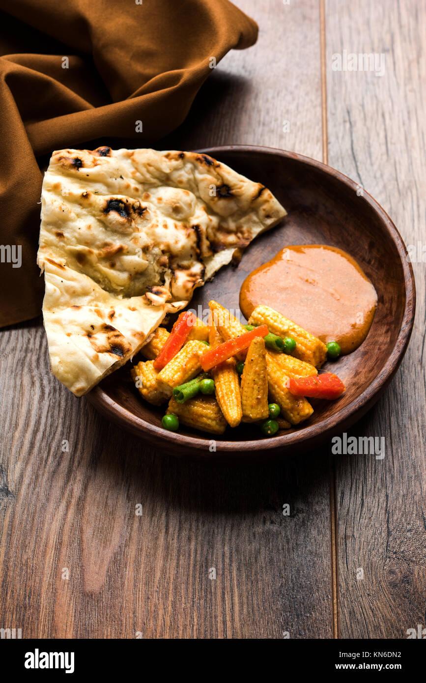 Bambino indiano Masala mais o piccante Baby corn curry servita con roti o naan o pane indiano Immagini Stock