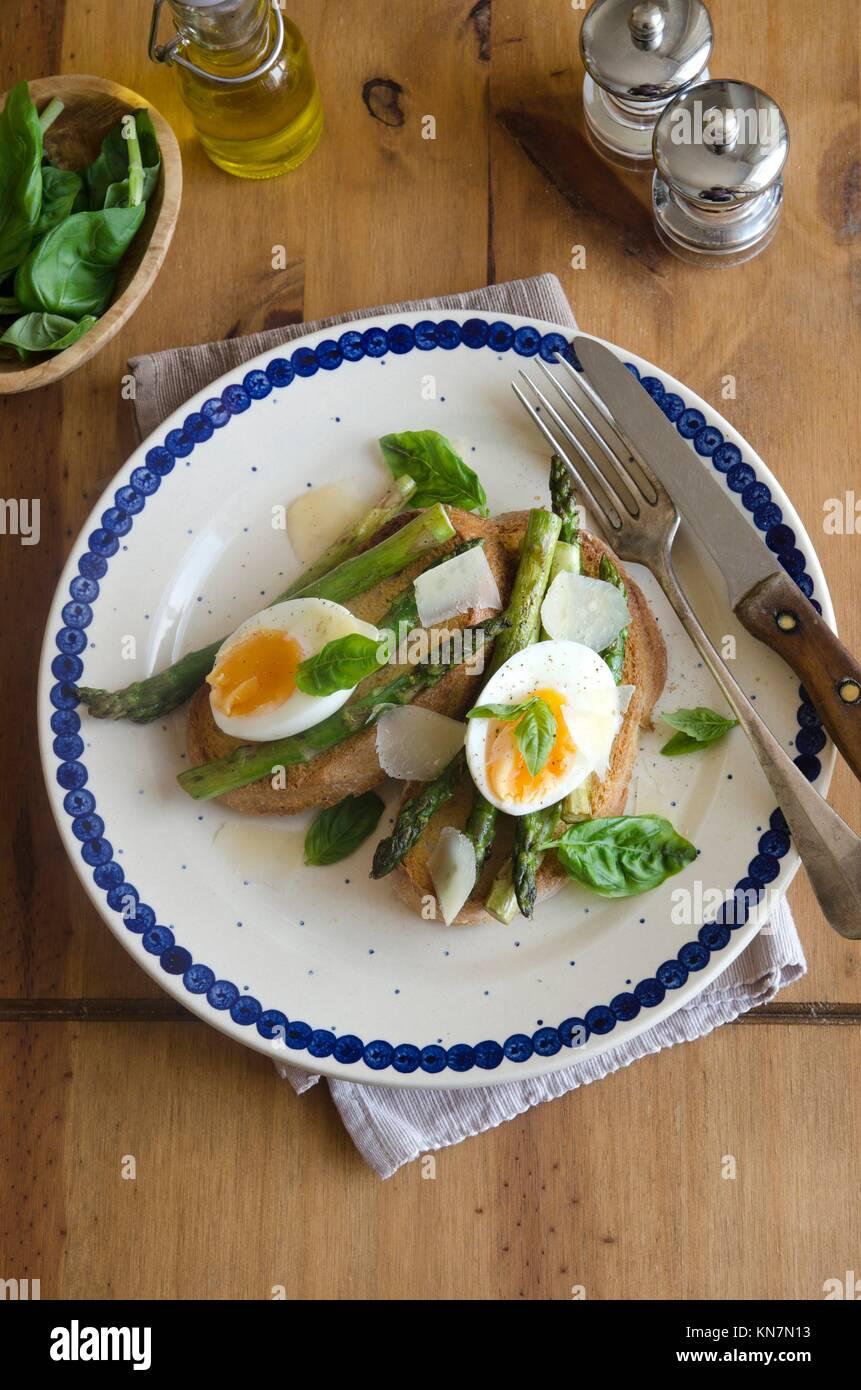 Soft-uova sode, asparagi e pecorino su pane tostato. Immagini Stock