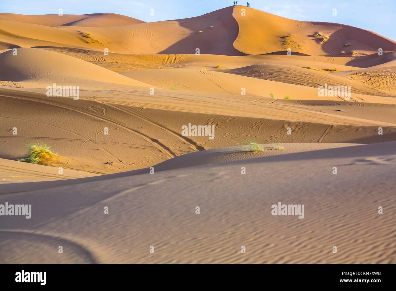 Persone ammirate il tramonto dalla collina. Diversi sand hill a Erg Chebbi nel deserto del Sahara. Ers sono grandi dune formate dal vento soffiato sabbia. Foto Stock
