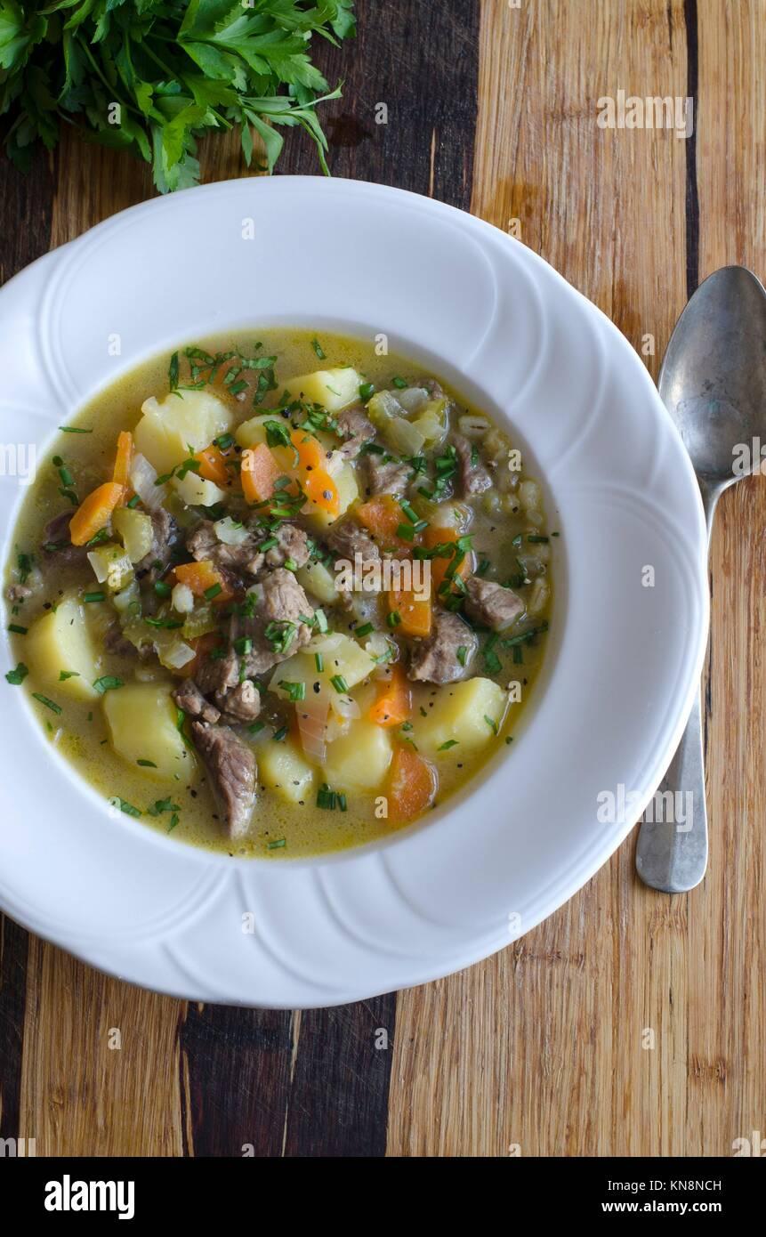 Agnello e patate e lo stufato di verdure condito con un trito di erba cipollina e prezzemolo. Immagini Stock