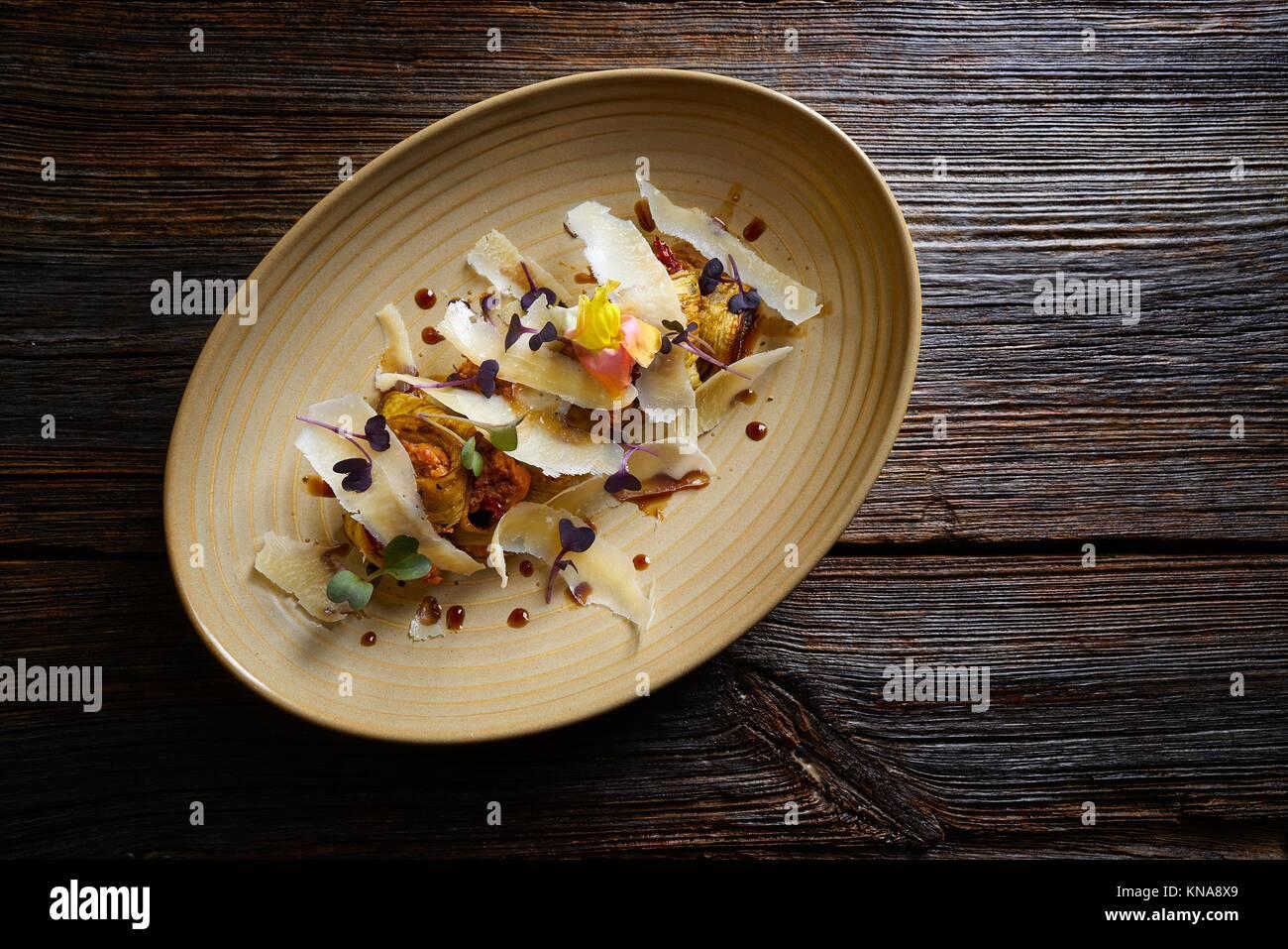 Melanzane e formaggio ricetta cibo italiano sulla tavola di legno. Immagini Stock