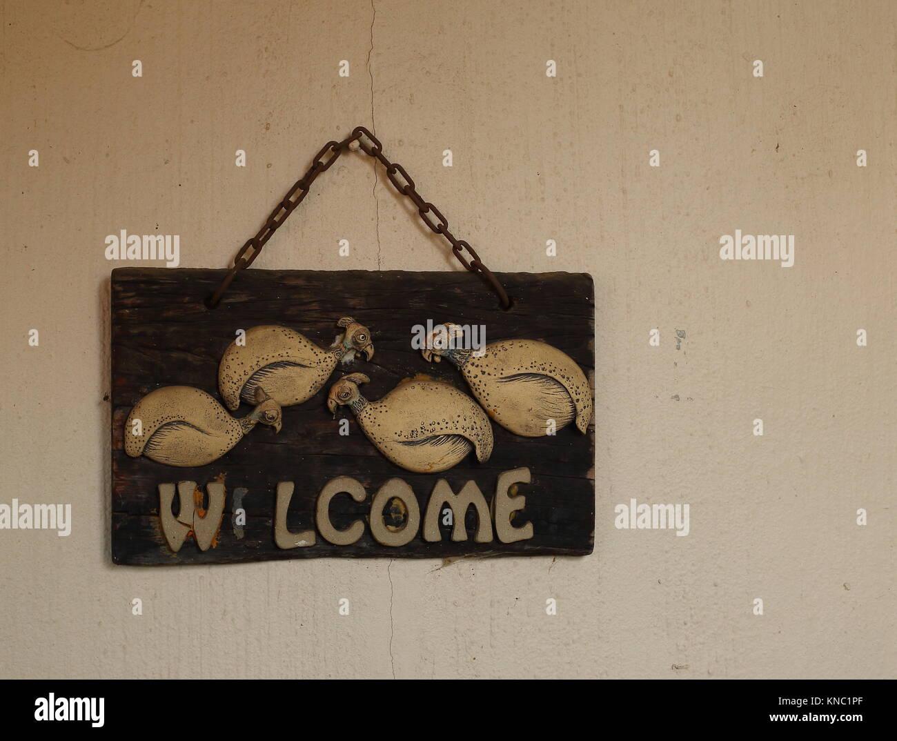 Un fatiscente e alterate in legno segno di benvenuto con una lettera mancante appeso su una sporca e muro rotto Immagini Stock