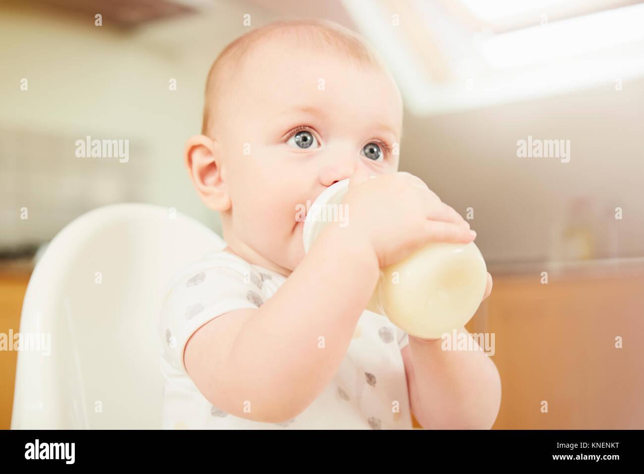 Bambino seduto nella sedia alta, bere latte dalla bottiglia Immagini Stock