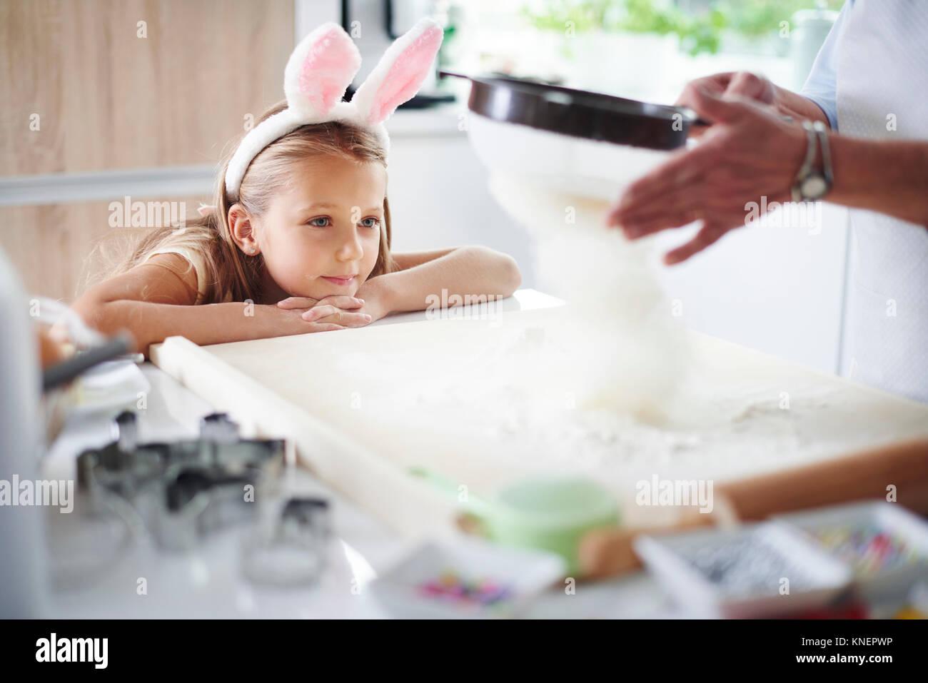 Ragazza Guarda la nonna setacciare la farina per la cottura di pasqua Foto Stock
