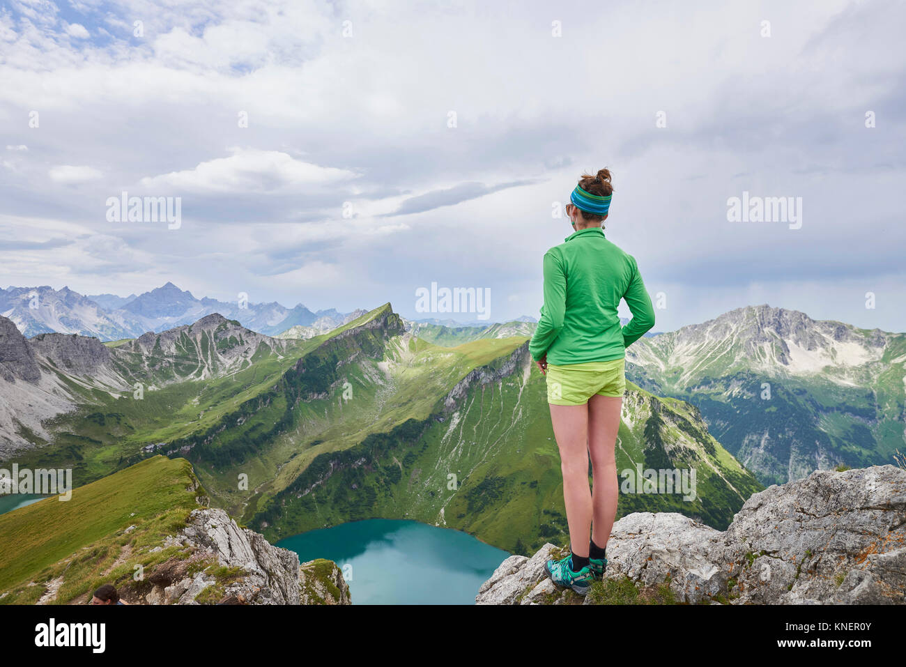 Vista posteriore di un escursionista femmina sul bordo roccioso affacciato su montagne di Tannheim, Tirolo, Austria Immagini Stock