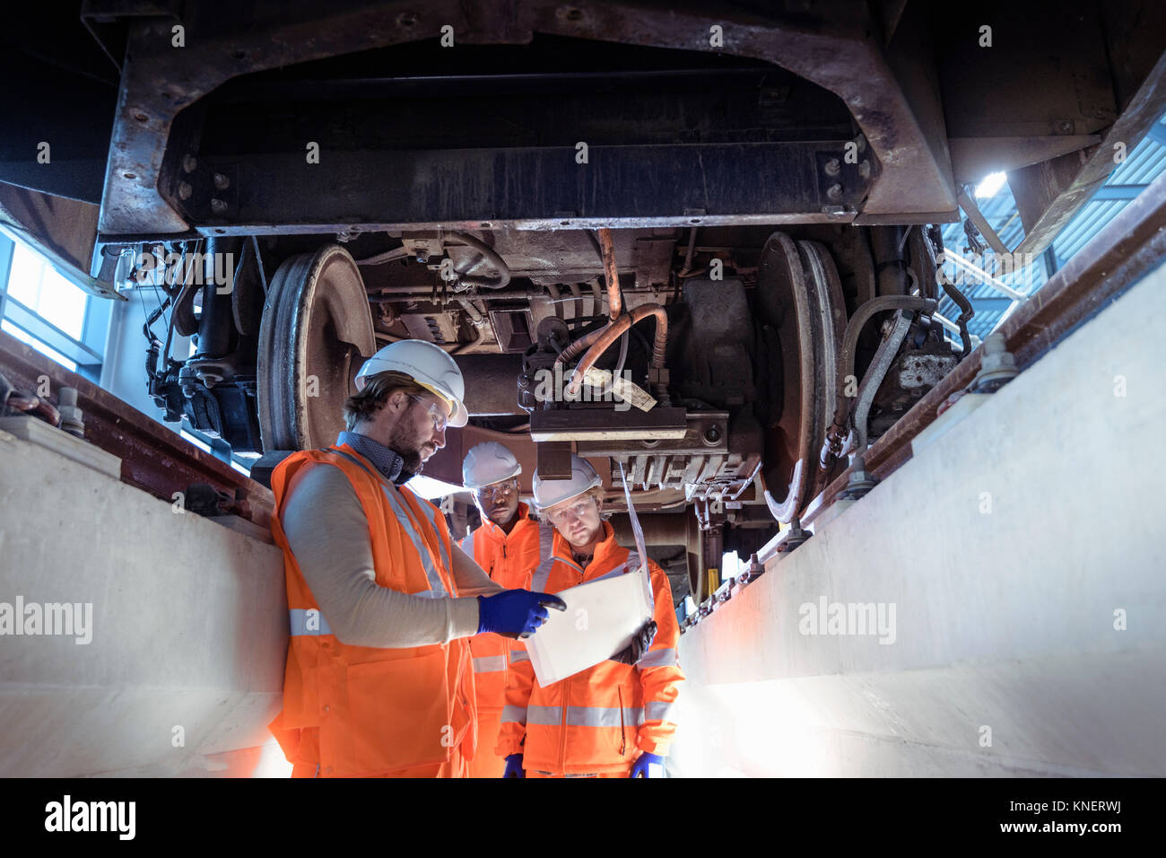 Istruttore e apprendisti sotto il treno in railway engineering facility Foto Stock