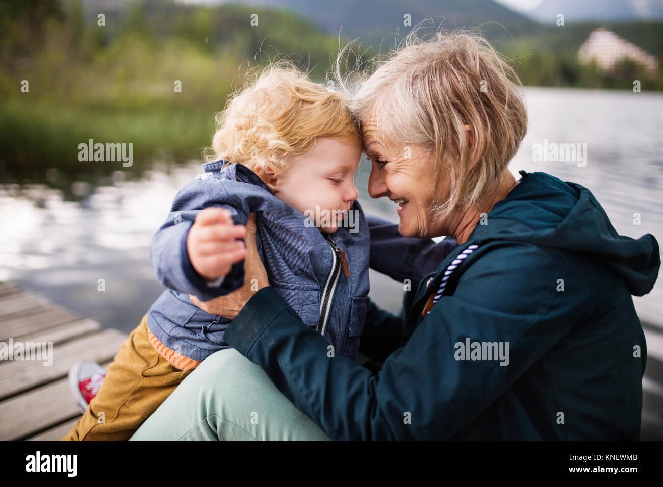 Senior Donna con bambino al lago. Immagini Stock