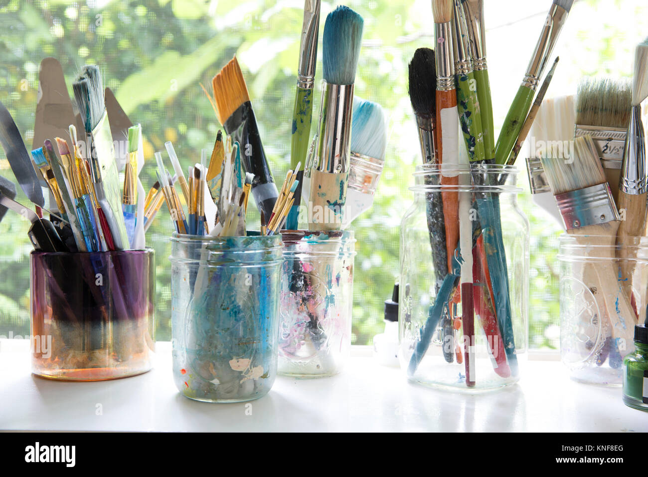 Fila di vasi con varietà di artista pennelli sul davanzale di artisti studio Foto Stock