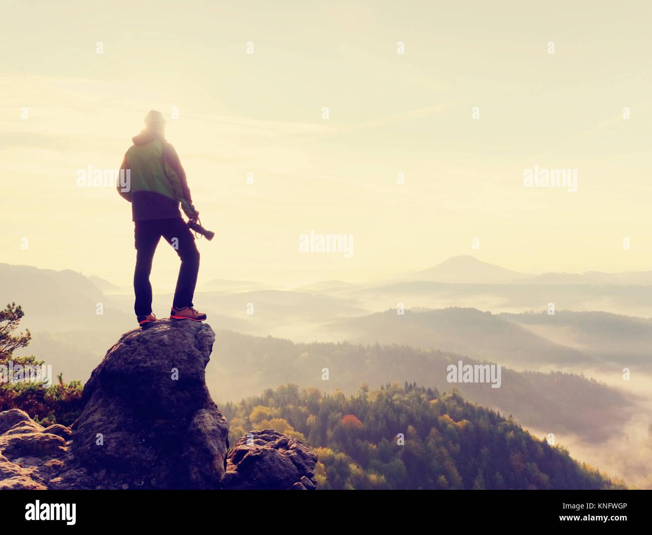 Fotografo di natura in azione. Silhouette uomo al di sopra di una nebbiosa nuvole, mattina paesaggio collinare. Immagini Stock