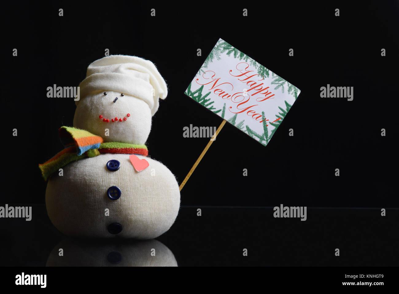 """Pupazzo di neve la figura di contenimento della scheda sulla targhetta con bastone attaccato e il testo """"Happy Immagini Stock"""