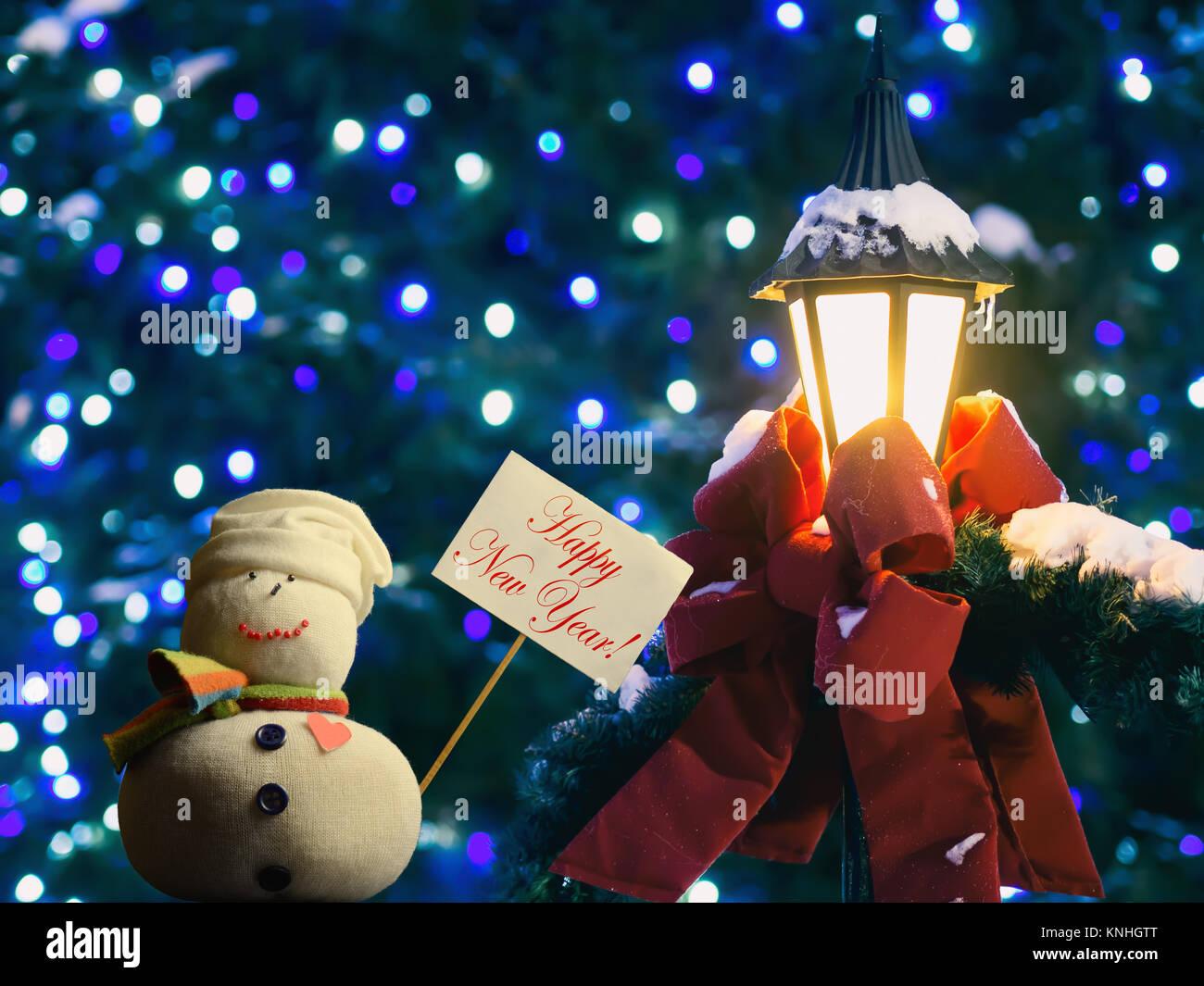 """Pupazzo di neve figura tenendo un cartello con scheda stick attaccato. Il testo """"Happy New Year!"""". Lanterna Immagini Stock"""
