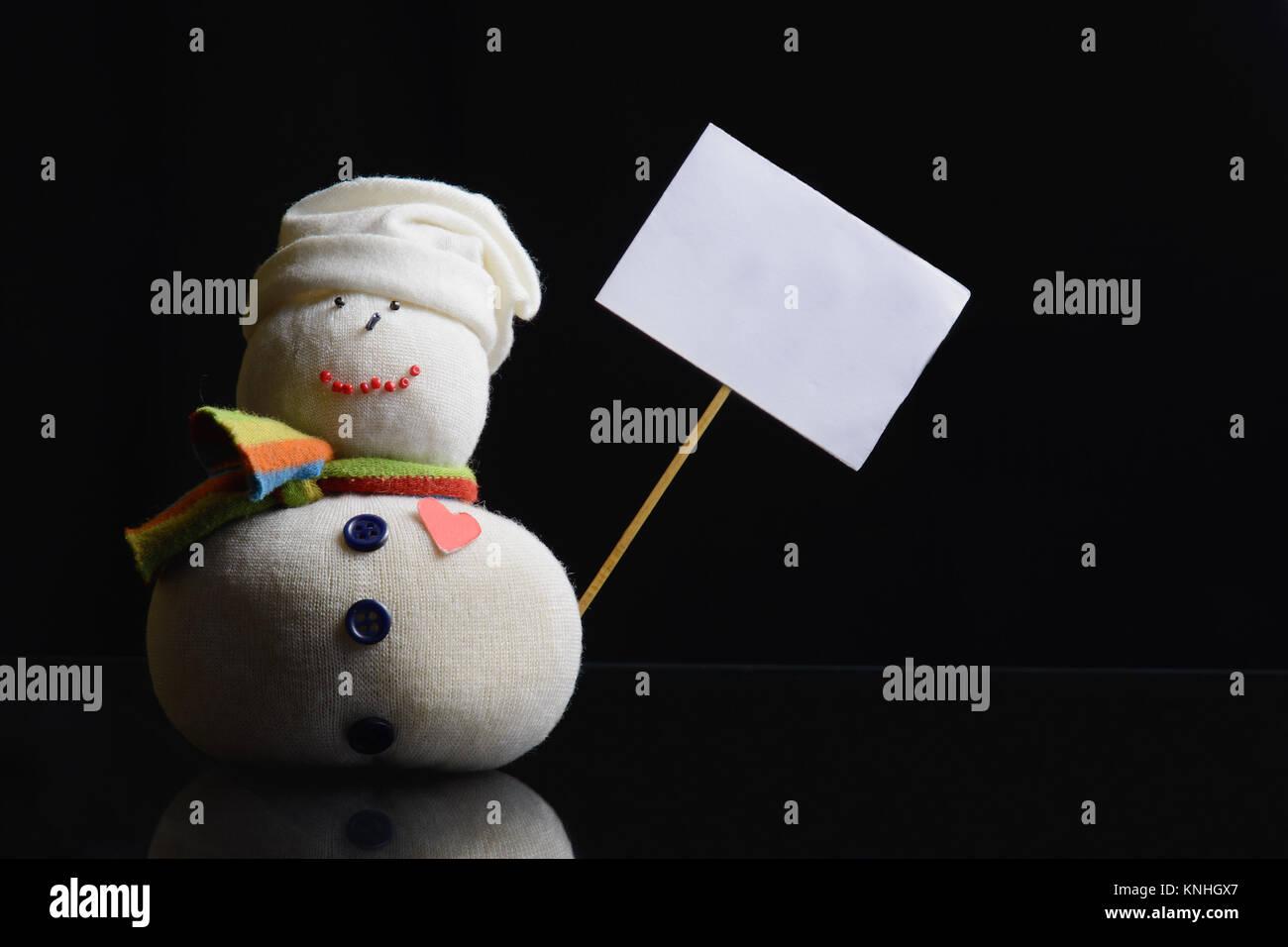 Pupazzo di neve la figura su uno sfondo nero in possesso di una targhetta vuota con scheda stick attaccato. Un contrasty Immagini Stock