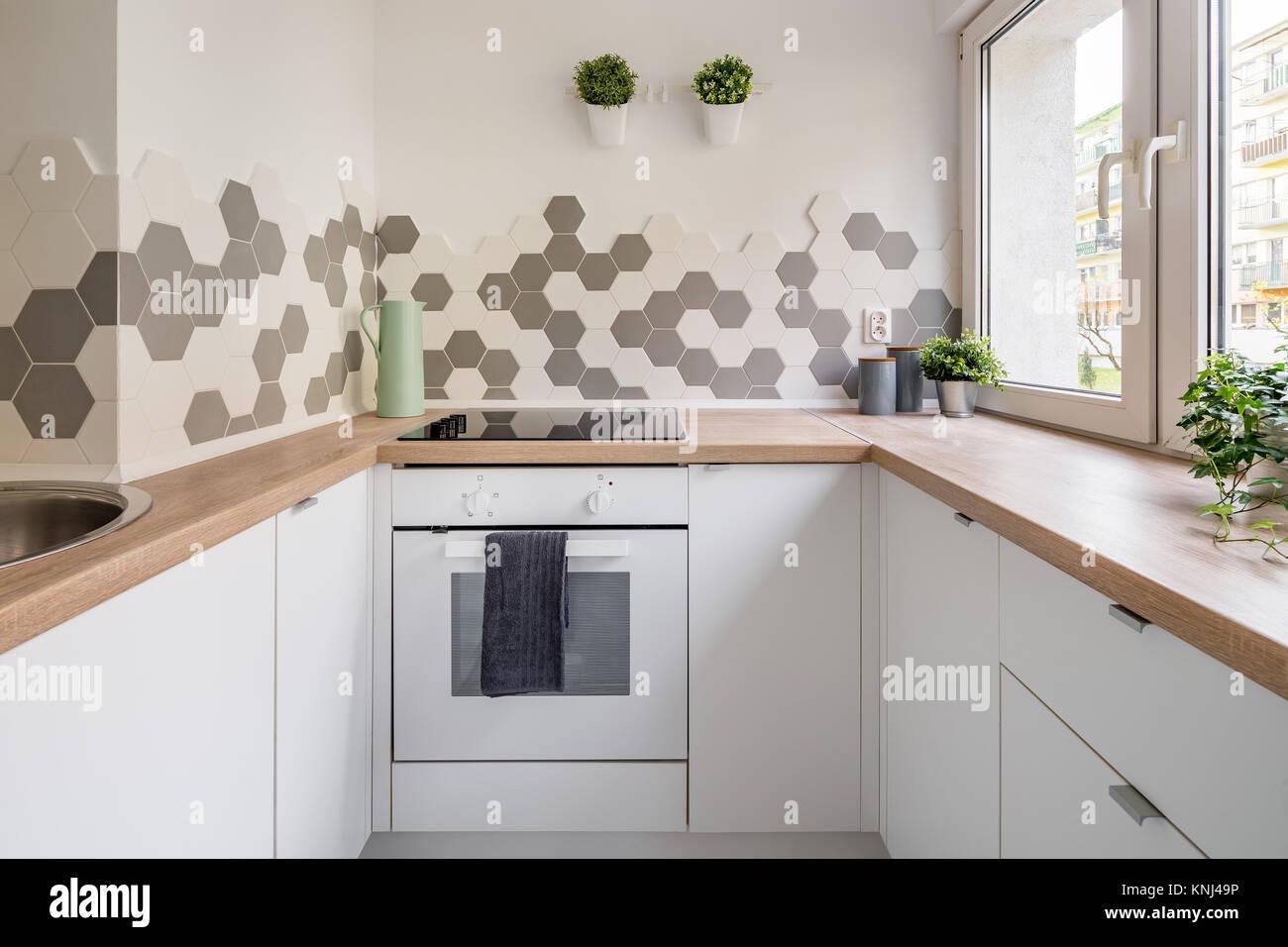 Cucina in stile scandinavo con armadi bianchi bancone in legno e