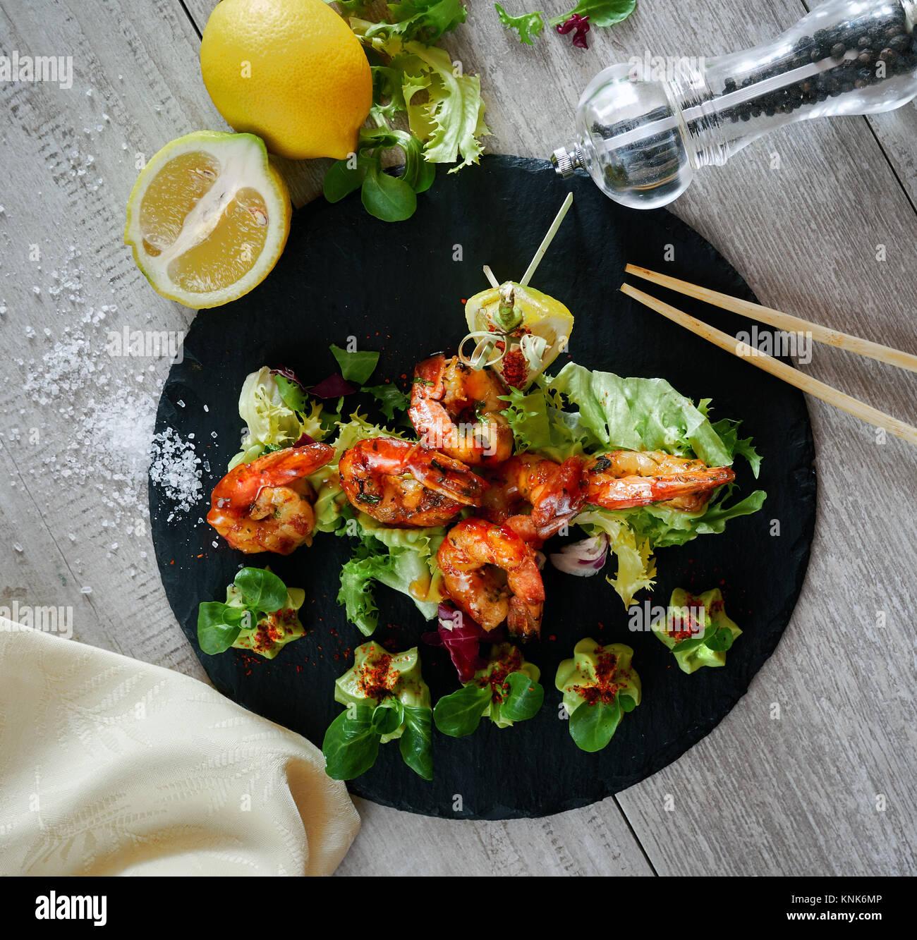 Grigliata di gamberi alla griglia con insalata di guacamole Immagini Stock
