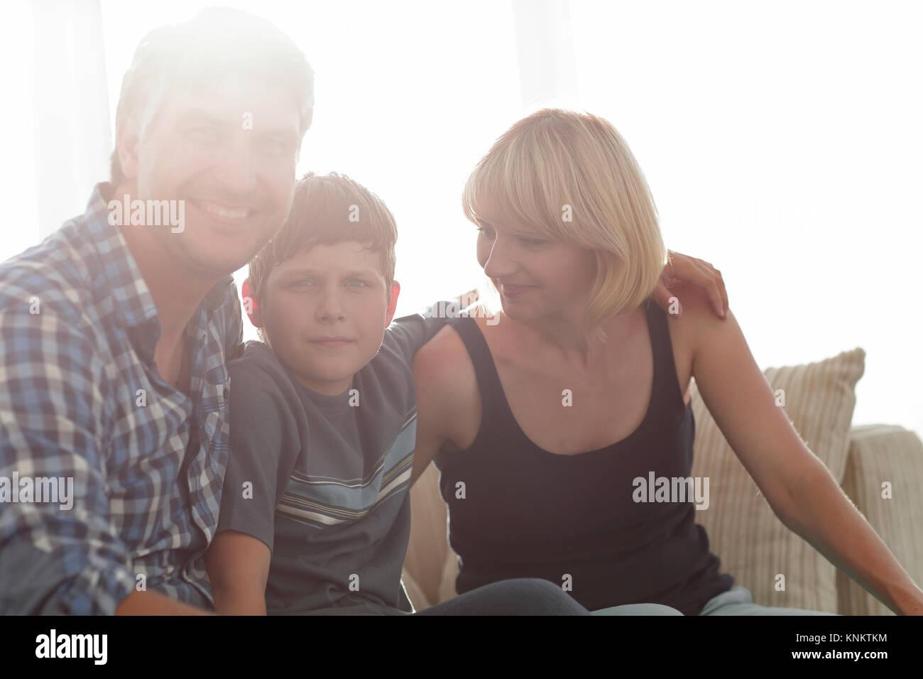 I genitori e il loro figlio sedersi rannicchiato nella stanza vivente e sorridente Immagini Stock
