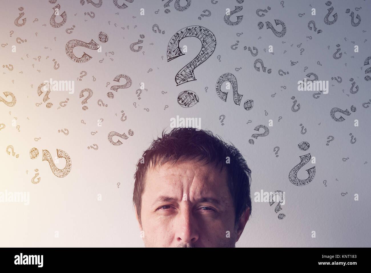 Punto interrogativo, cercando risposte. Perplesso uomo con scarabocchiati interrogatorio di simboli punto intorno Immagini Stock