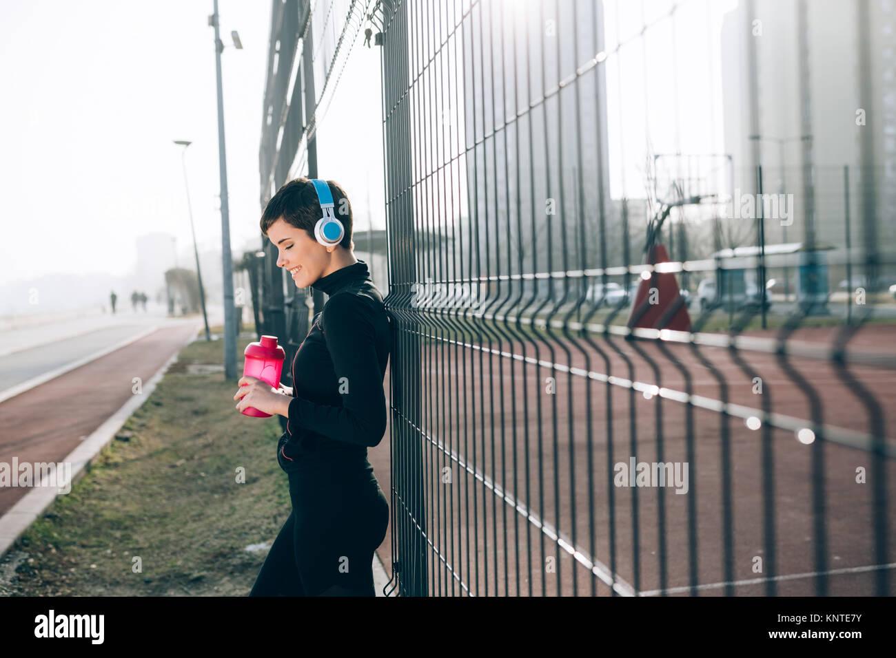 Donna ascoltare musica mentre lavora fuori e jogging all'aperto Immagini Stock